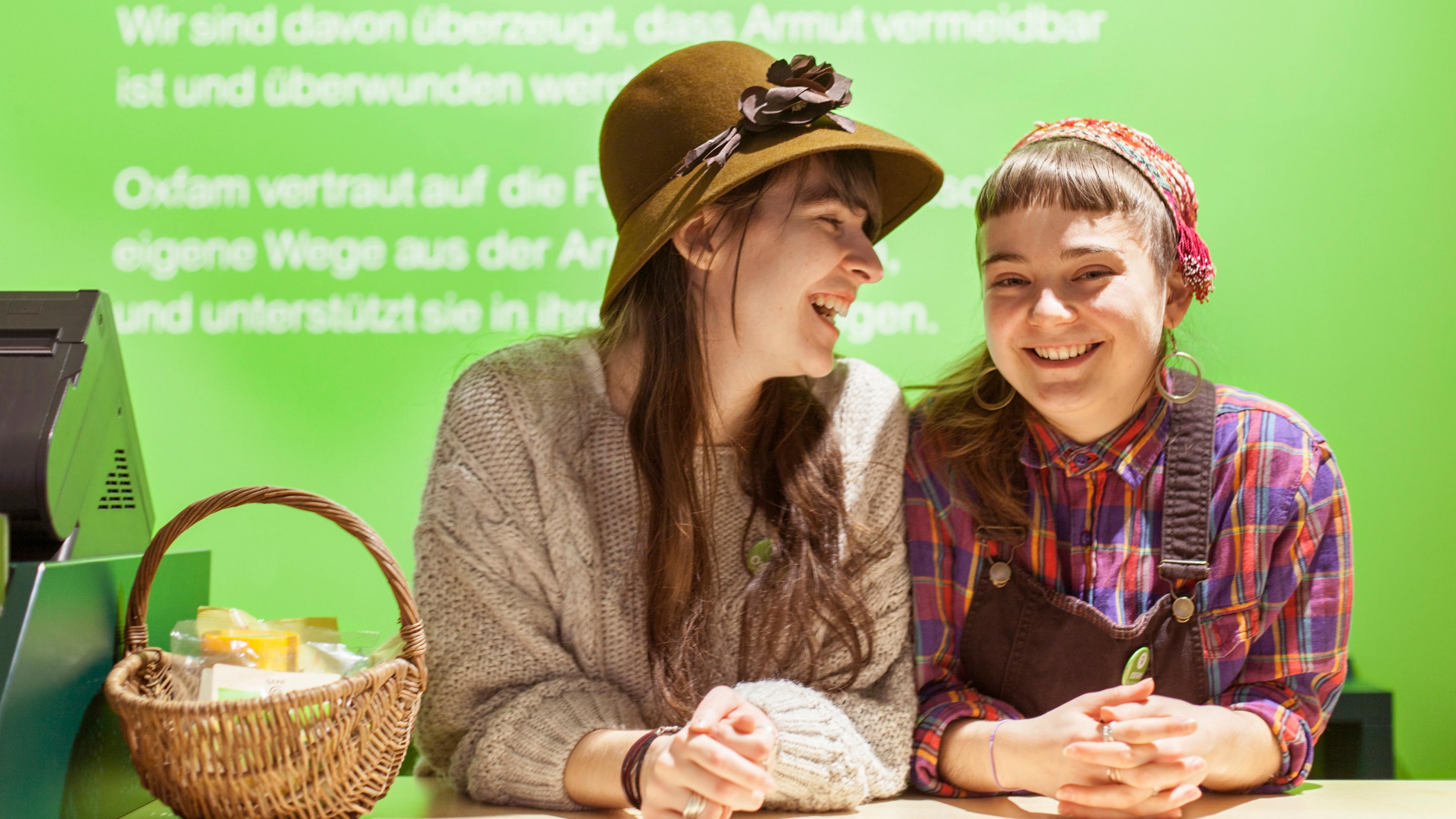 Zwei Ehrenamtliche am Empfangstresen im Oxfam Shop