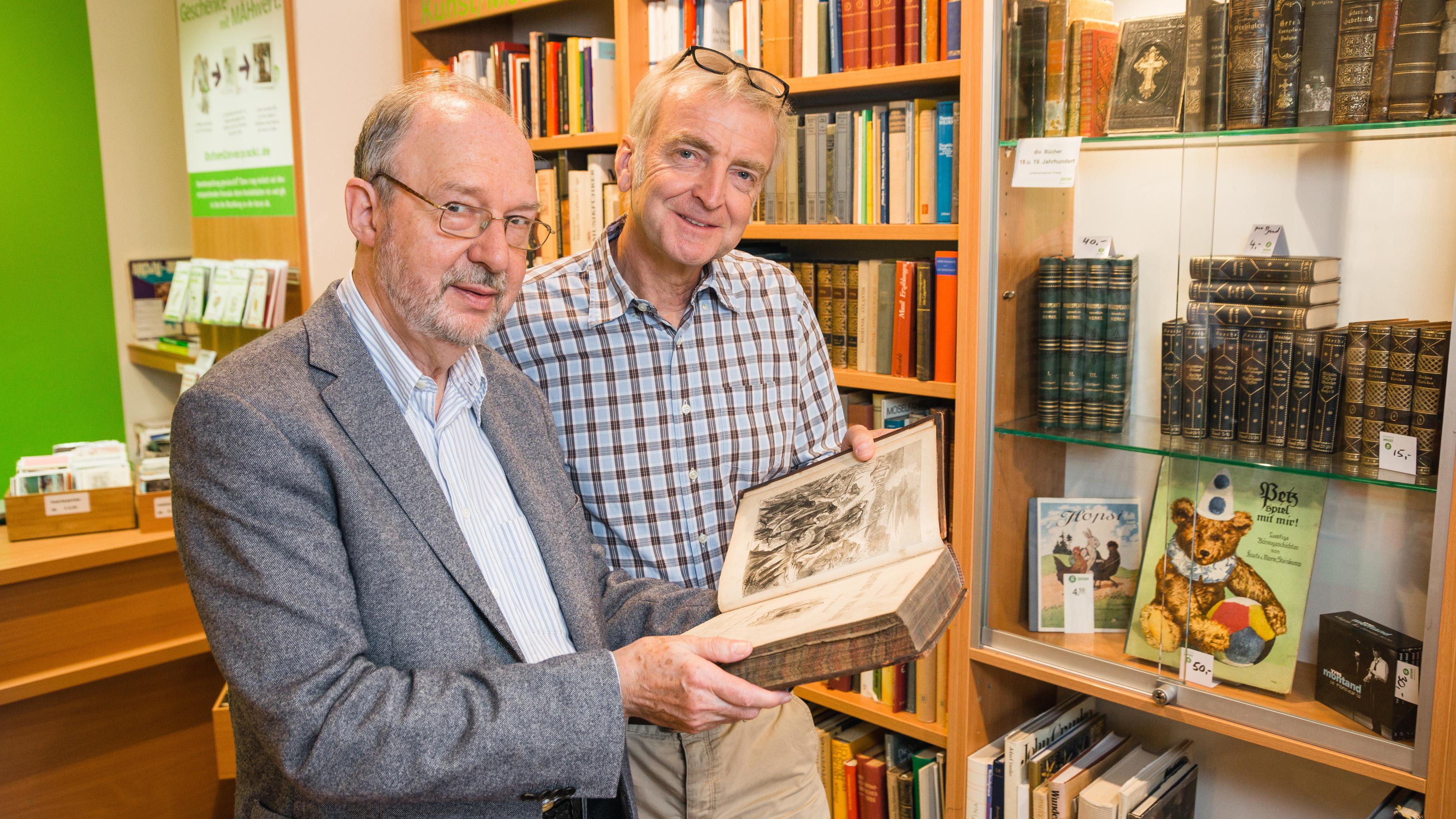 Der Ehrenamtliche Klaus Roland (li) zeigt Dirk Horn ein wertvolles gespendetes Buch.