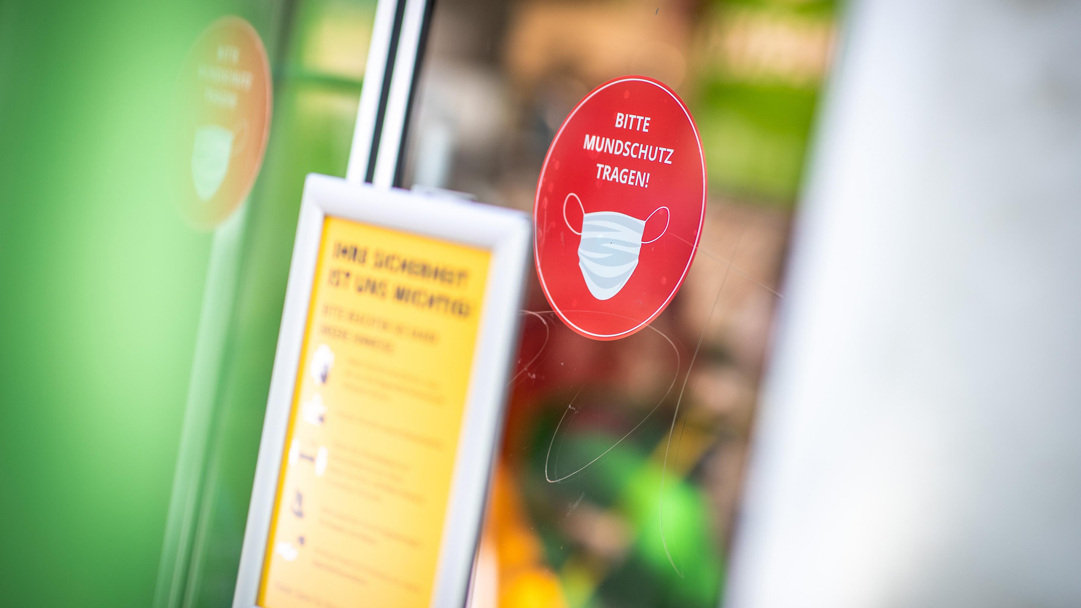 Mundschutz-Aufkleber an Eingangstür eines Oxfam Shops