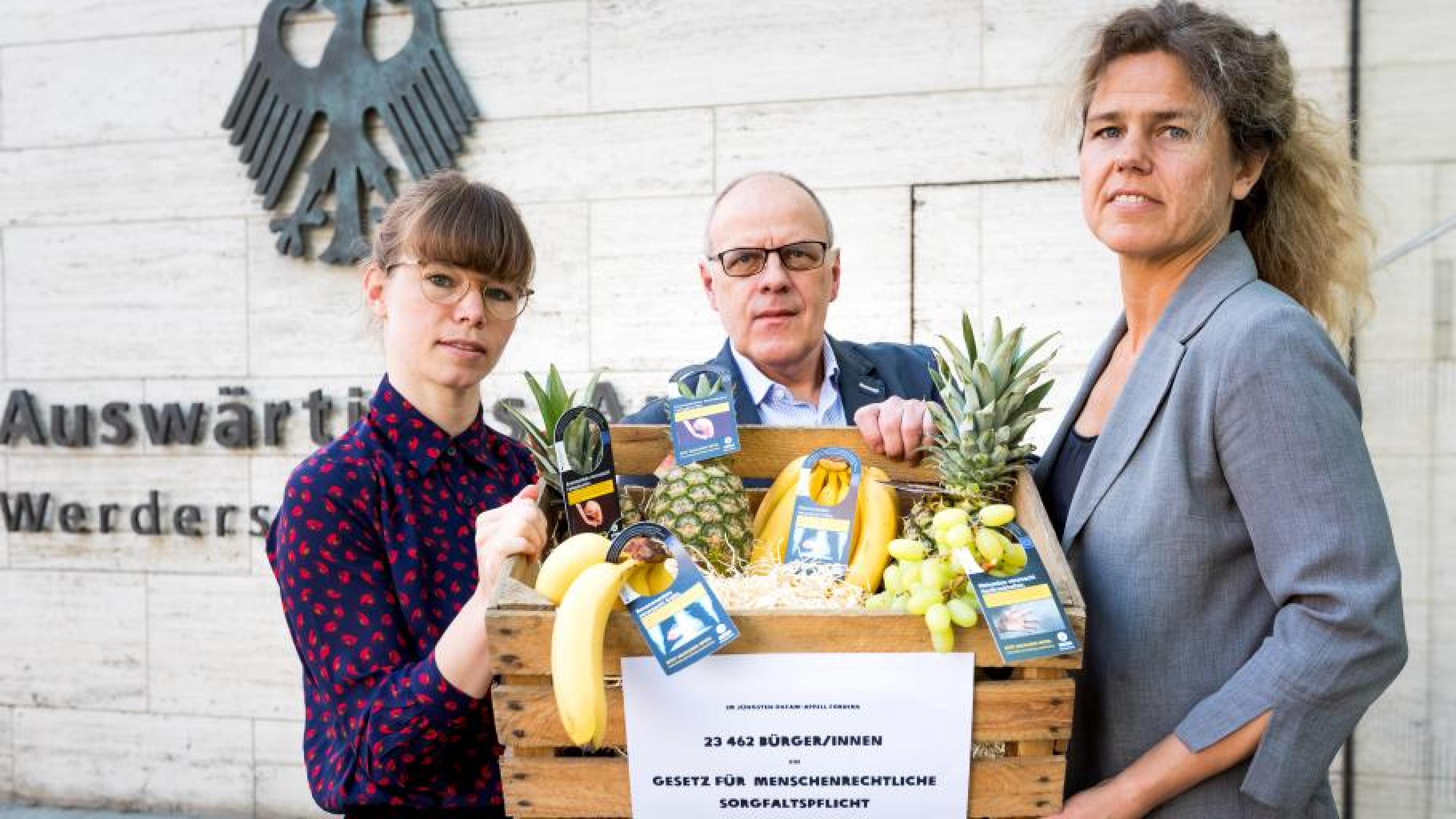 """Oxfam-Mitarbeiter bei der Unterschriftenübergabe """"Globale Ausbeutung stoppen: Unternehmen in die Pflicht nehmen"""""""