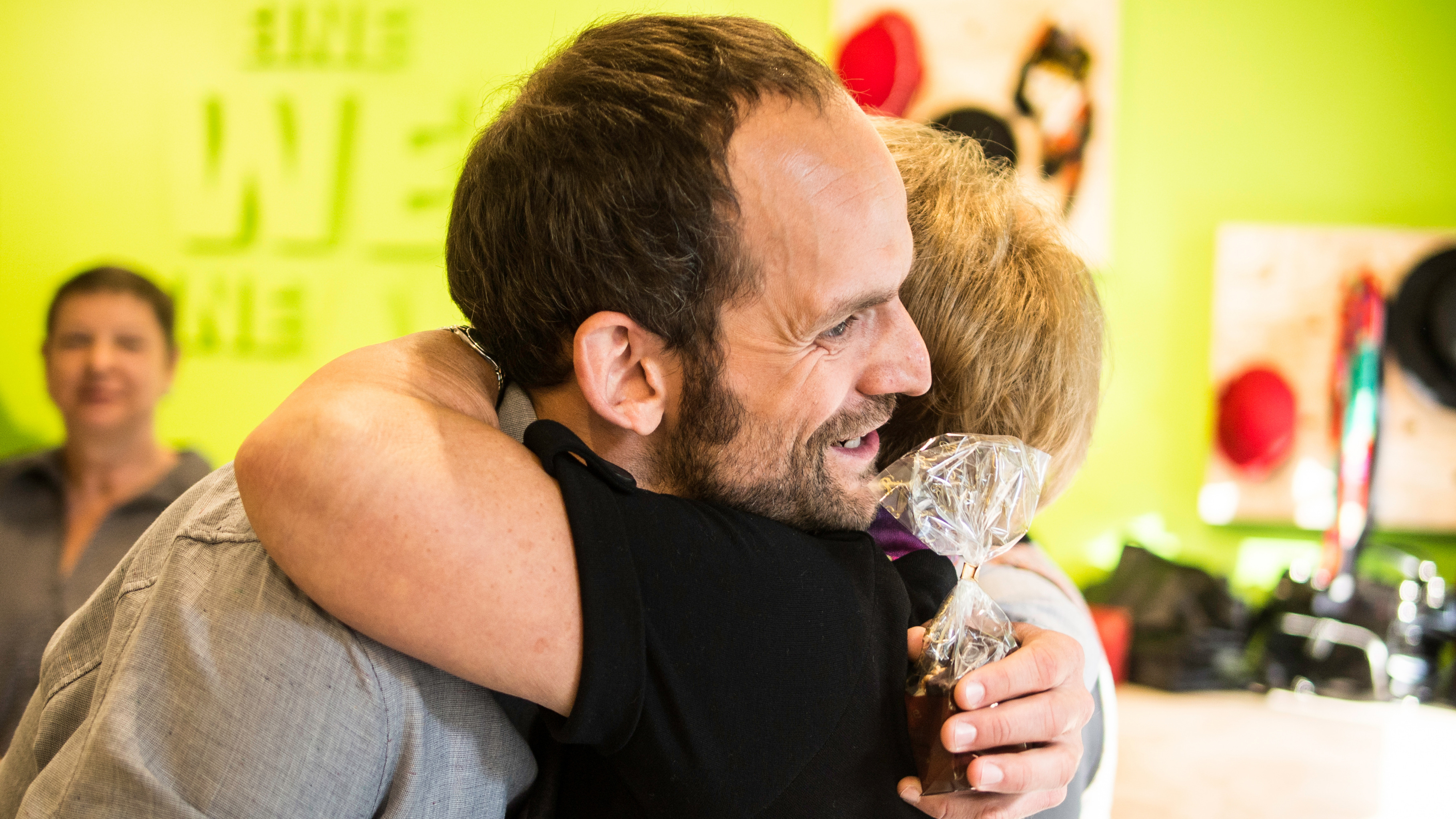 Danke: Shop-Referent umarmt Ehrenamtliche im Oxfam Shop