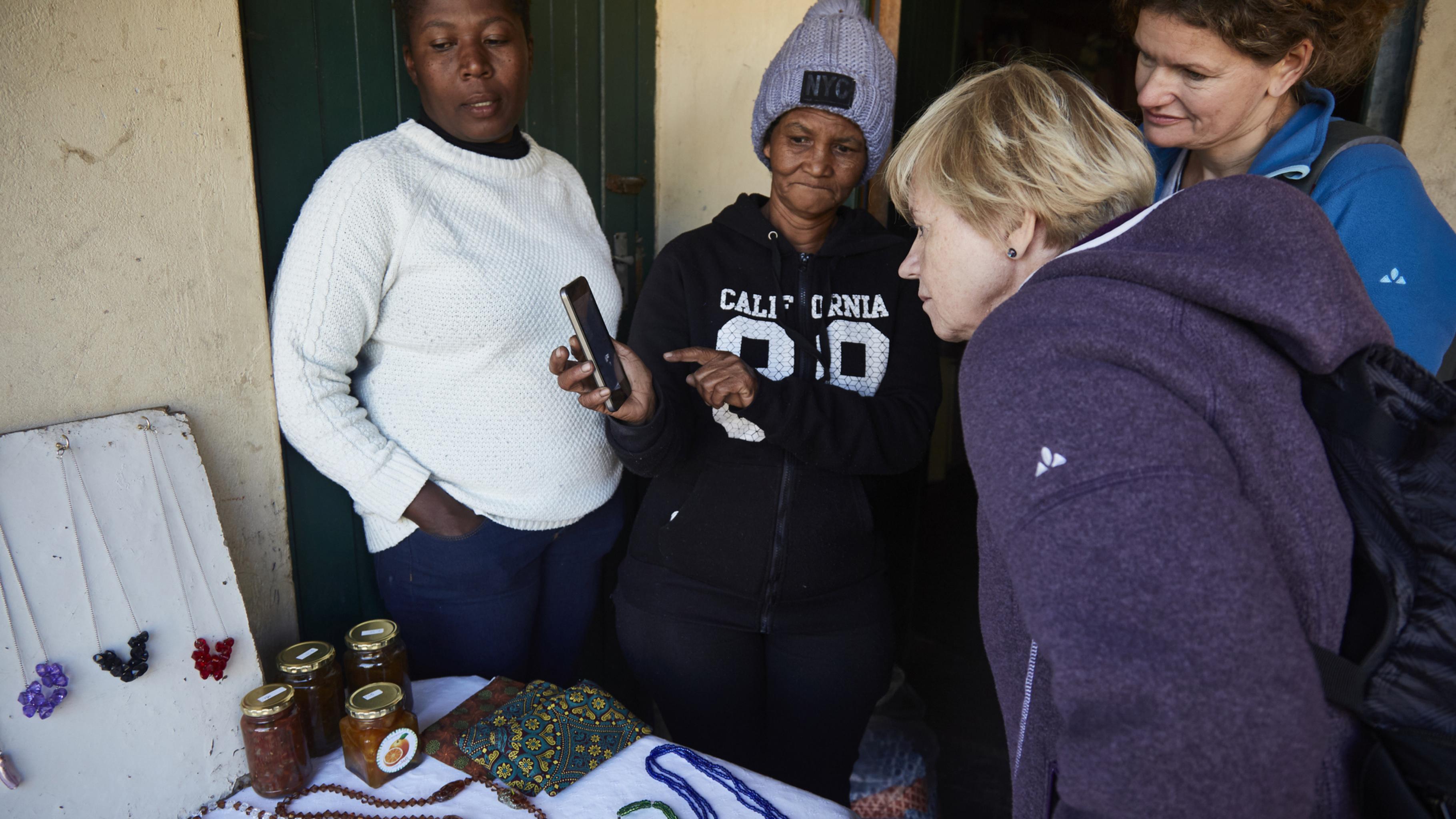 Bongeka Ntshweza, Magrieta Arendse, Gaby und Ulrike (v.l.) schauen sich Magrietas Schmuck an, den sie in ihrer Community verkauft.