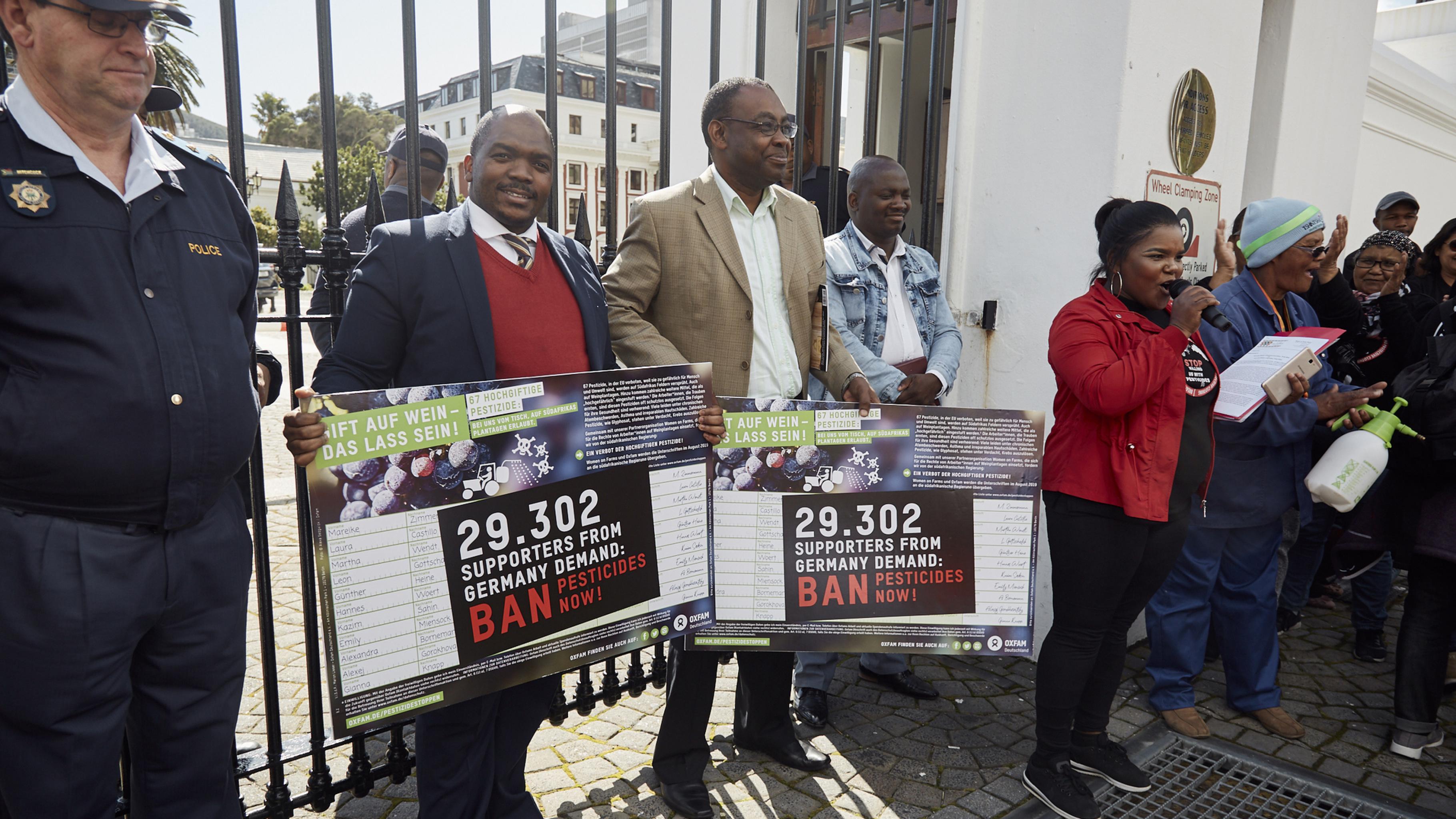 Die Vertreter des Arbeits- und Landwirtschaftsministeriums halten die Unterschriften aus Deutschland in den Händen.