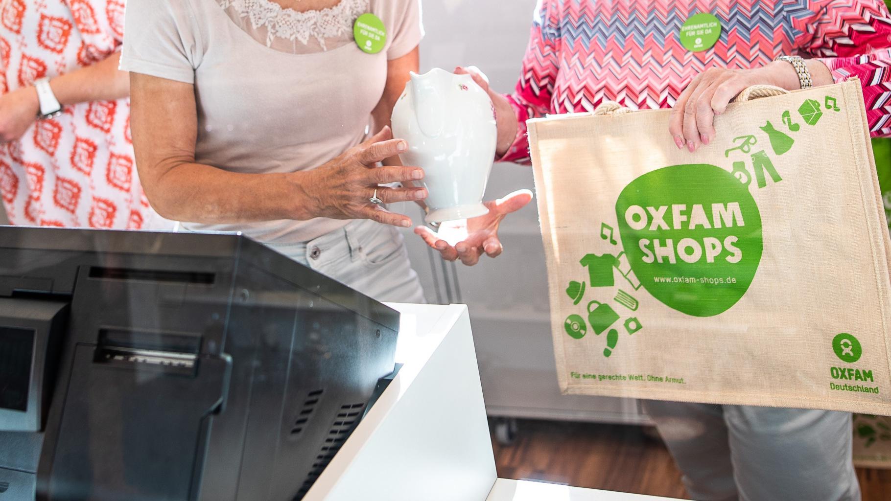 Ehrenamtliche mit Jute-Shopper an der Kasse eines Oxfam Shops