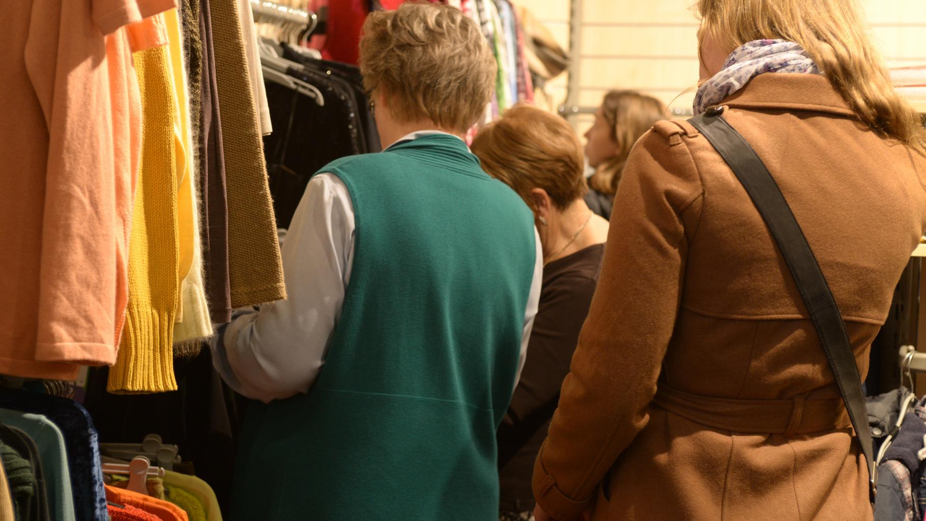 Kundschaft stöbert im Oxfam Shop durch das Kleidungsangebot.