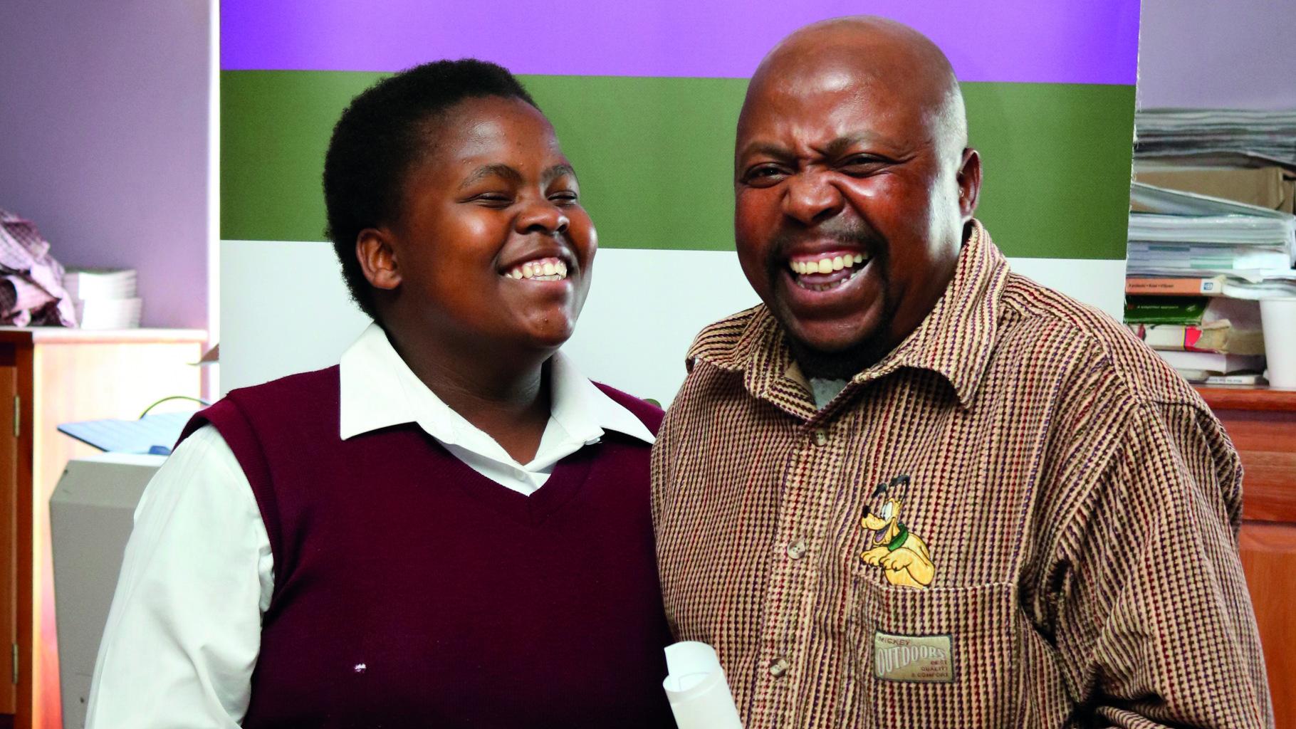Der Vater freut sich mit seiner Tochter Thulethu: Die Teenagerin hat erfolgreich an der Peer Education Schulung teilgenommen. Nun wird sie sich mit Gleichaltrigen gegen Gewalt an ihrer Schule und in ihrer Nachbarschaft im Township stark machen.