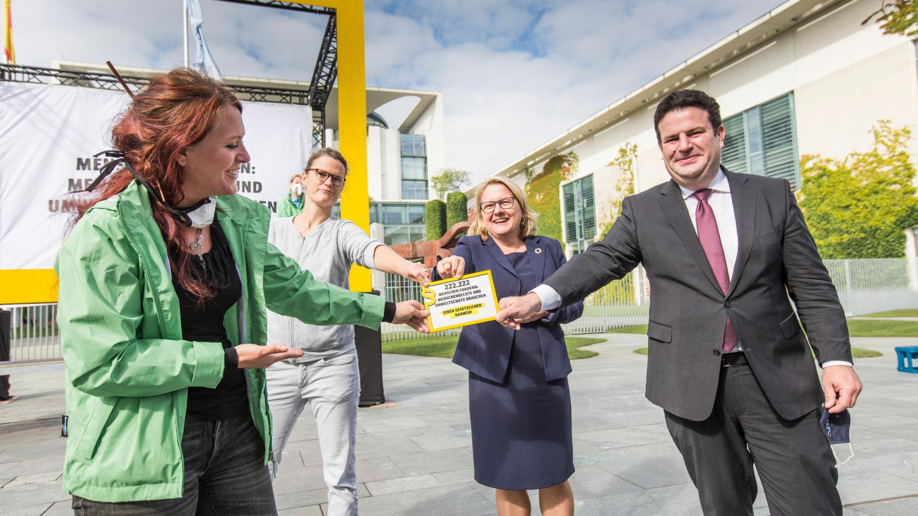 Umweltministerin Svenja Schulze und Arbeitsminister Hubertus Heil nehmen vor dem Kanzleramt ein Symbol für 222.222 Unterschriften für ein Lieferkettengesetz von zwei Aktivistinnen in Empfang.