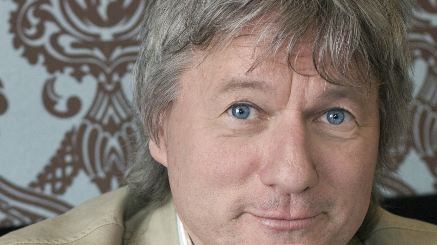 Kölner Kabarettist Jürgen Becker steht im Oxfam Shop Köln-Südstadt hinter der Kasse