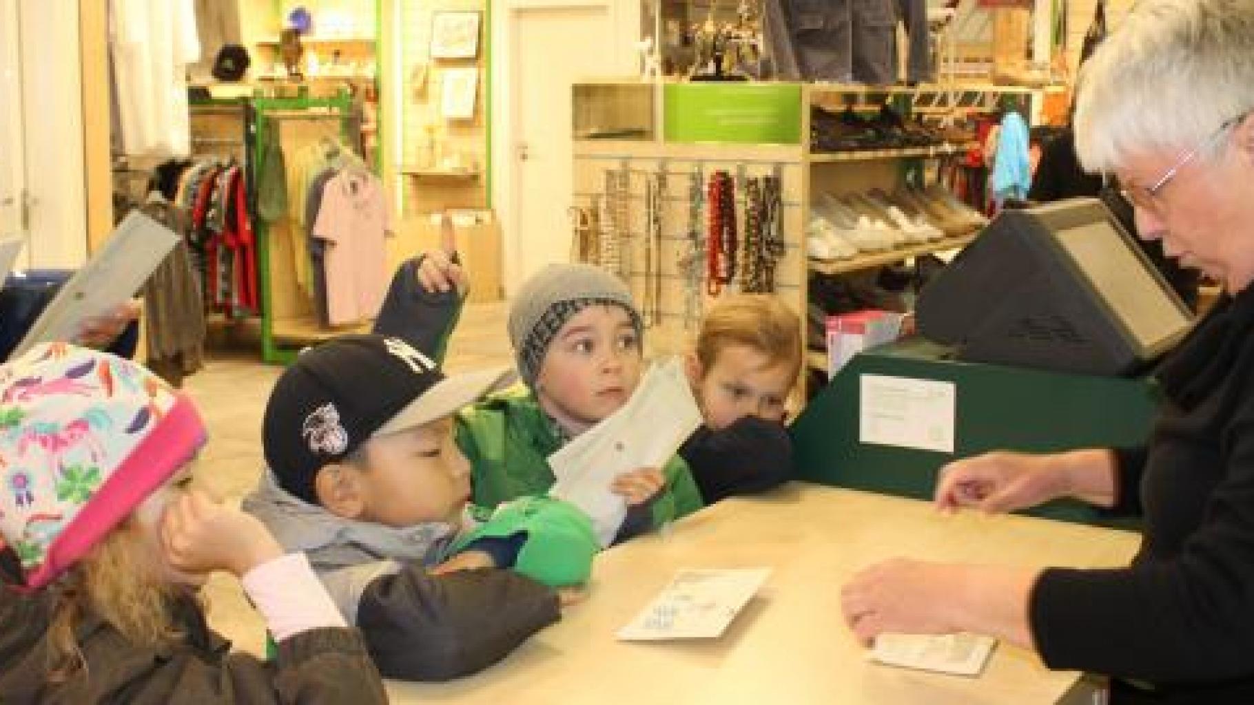 Die Kinder des Vellmenkrippe e.V. in Stuttgart übergeben der ehrenamtlichen Shop-Mitarbeiterin stolz ihr gesammeltes Geld.