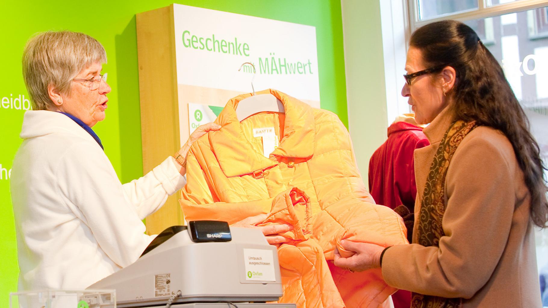 Kundin kauft Winterjacke im Oxfam Shop