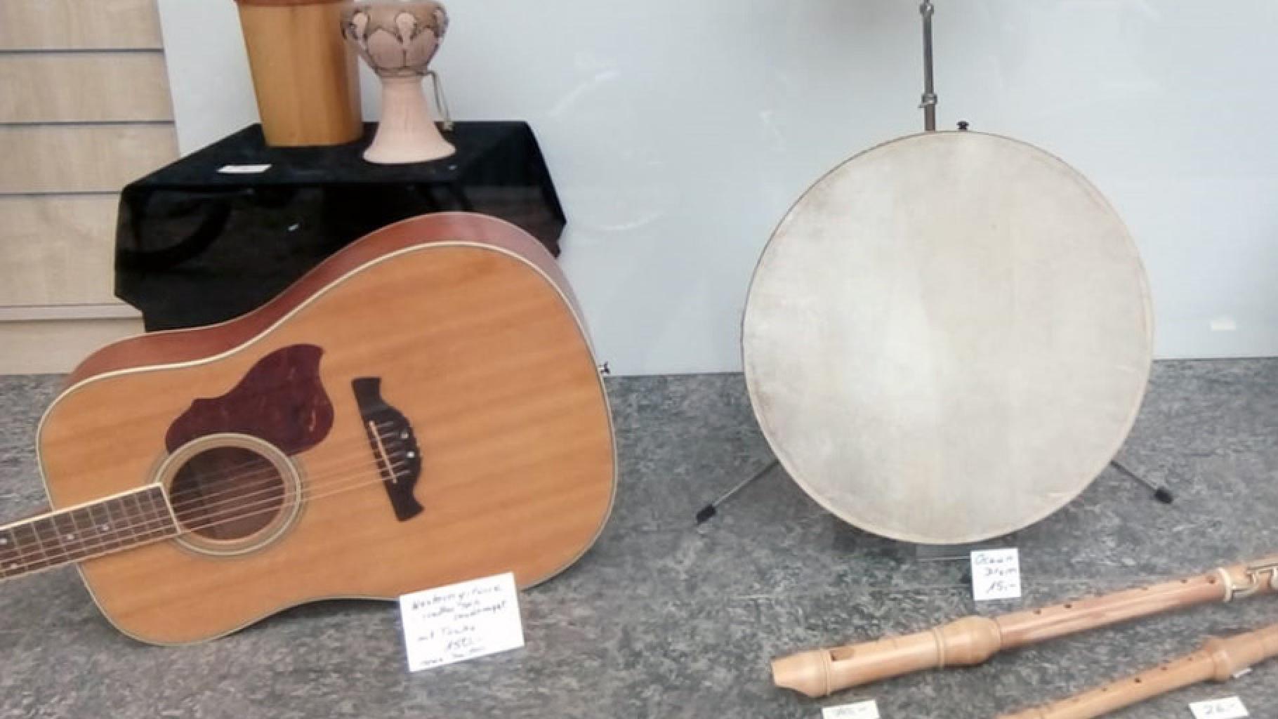 Musikinstrumente im Schaufenster eines Oxfam Shops