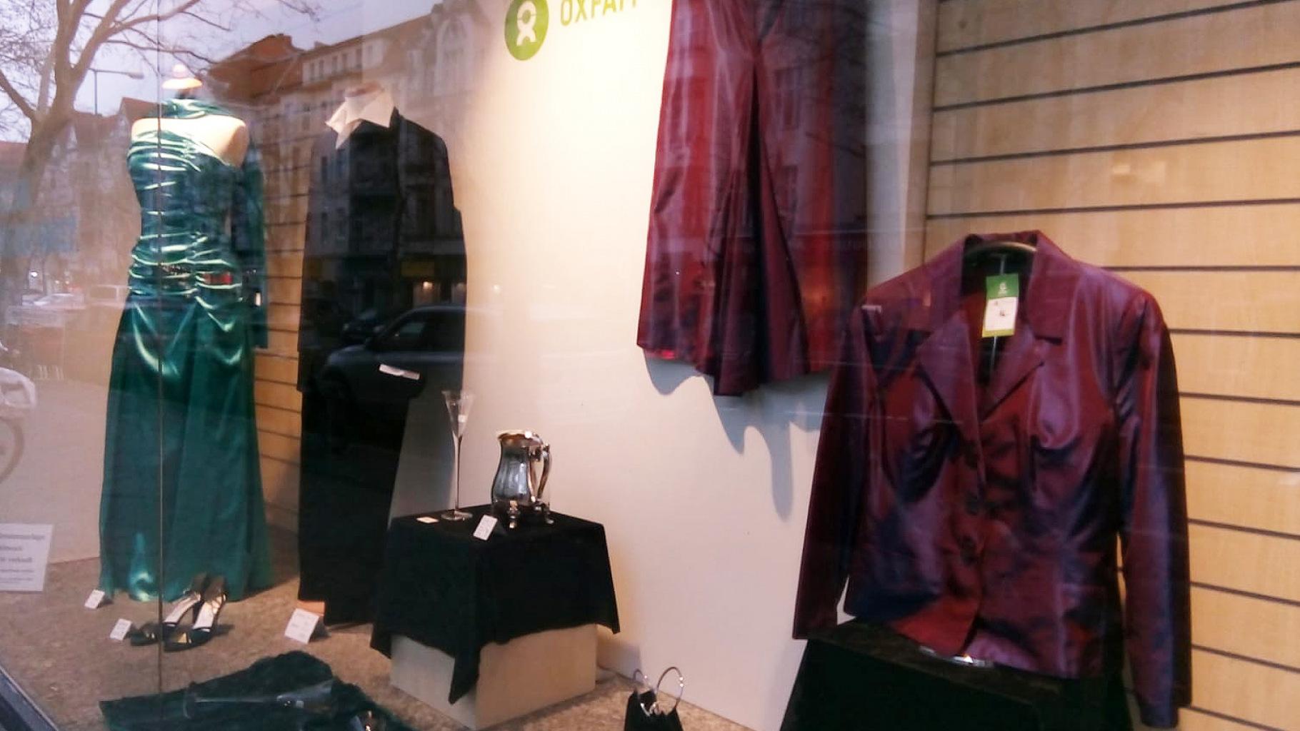 Schaufenster eines Oxfam Shops mit festlicher Kleidung