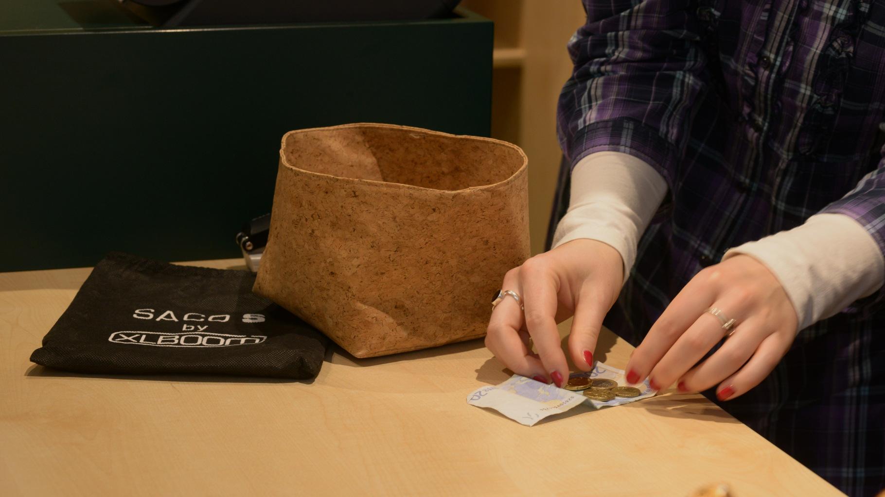 Frau bezahlt an der Kasse im Oxfam Shop