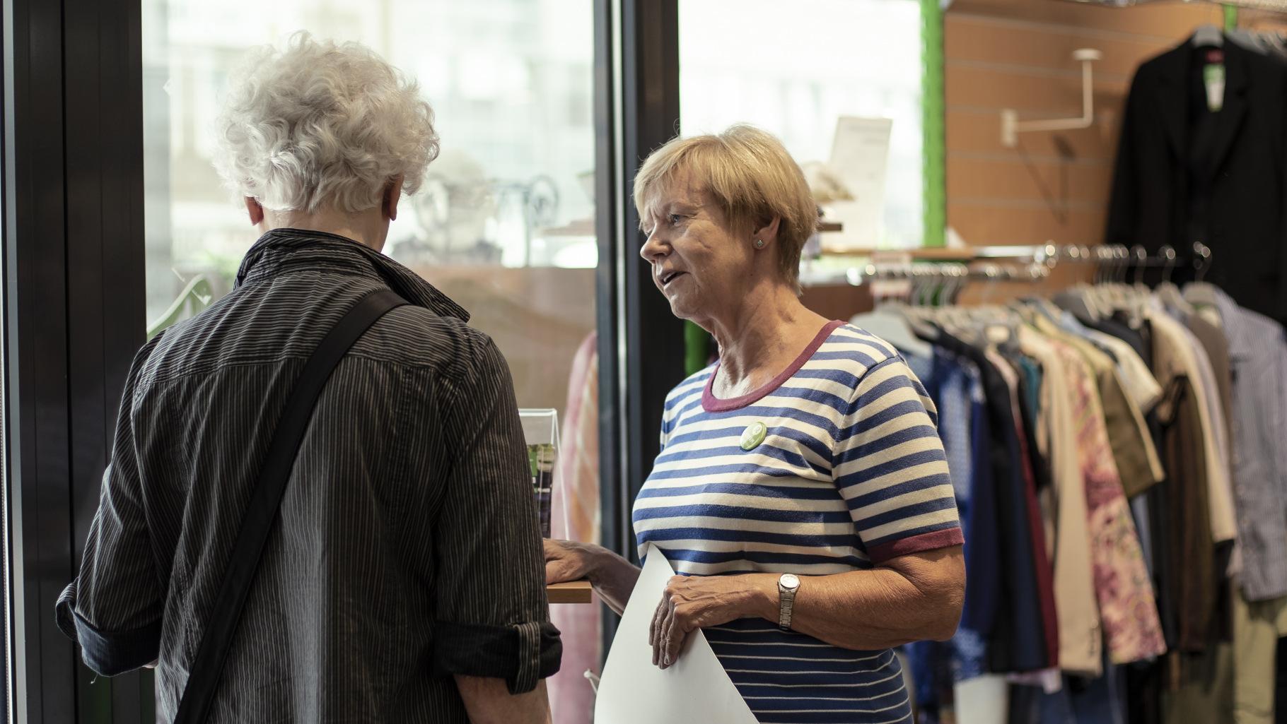 Gabriele Sarteh informiert einen Kunden im Oxfam Shop Bonn über Oxfams Kampagne.